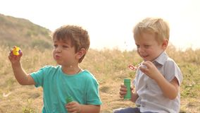 Boys playing with soap bubbles at sunset in Park. stock footage