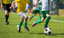 Boys playing soccer football match. Young boys playing football soccer game. Running players in yellow and white uniforms Royalty Free Stock Photo