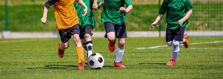 Boys playing soccer game. Horizontal sports football background. Royalty Free Stock Image