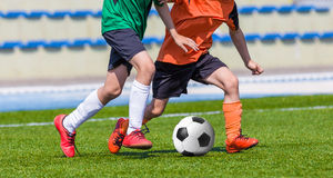Boys Playing Soccer Game. Young boys children in uniforms playing youth soccer football game tournament. Horizontal sport background Royalty Free Stock Photos