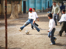 Boys playing soccer in Giza. Group of boys playing soccer in street near school and having fun playing and doing activities together and helping each other Royalty Free Stock Photos