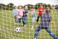 Boys playing soccer in park royalty free stock photography