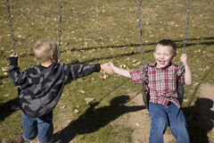 Boys playing on swing Royalty Free Stock Photo