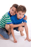 Boys playing together. A closeup studio view of two boys playing together on the floor.  White background Stock Image