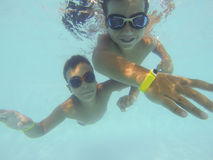 Boys playing underwater in the pool Stock Photos