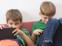 Boys playing video games on tablet computers Stock Images