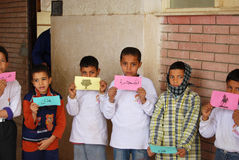 Boys playing words game at charity event. Group of boys playing words game at school, holding up Arabic words written on cardboard at charity event, at a camp to Royalty Free Stock Image
