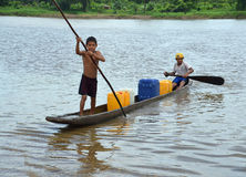 Boys in a ponga. WIS WIS VILLAGE, NICARAGUA - JULY 8, 2015:  Two unknown Nicaraguan boys paddle and pole their ponga to shore after retrieving drinking water for Royalty Free Stock Images