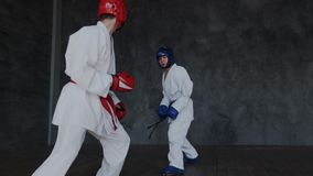 Boys practice fight attack in mix combat style. Young future winners learning martial skills indoor. Dangerous traumatic