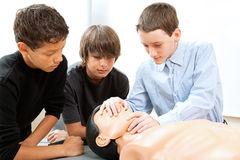 Boys Practicing CPR. Teenage boys learn CPR life saving techniques on a mannequin Stock Images