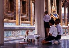 Boys praying, Bangkok. Royalty Free Stock Photo