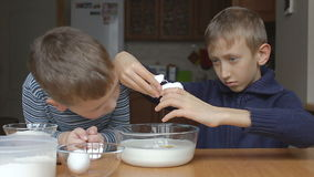 Boys prepare the dough and the older boy adds eggs to the milk stock video footage