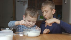 Boys prepare dough and older boy teaches younger stock video footage