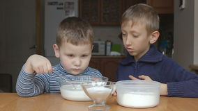 Boys prepare dough and younger boy add flour stock video