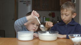 Boys prepare dough and younger boy add flour and thumb up stock video footage