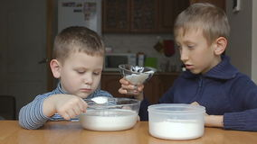Boys prepare dough and younger boy add sugar stock video footage