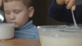 Boys prepare the dough and the younger looks at the dough stock footage