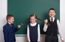Boys pull the girl braids, elementary school boy near blank chalkboard background, dressed in classic black suit, group pupil, edu Stock Photography