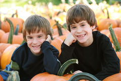 Boys in the Pumpking Patch. Boys Resting on a Pumpkin in the Pumpking Patch Royalty Free Stock Image