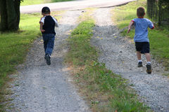 Boys Racing. Five year old boys racing to the end of drive. Shot with a Canon 20D stock image
