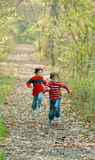 Boys Racing. Boys Having Fun Racing in the Woods Royalty Free Stock Image