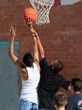 Boys Reaching for Basket. Boys playing basketball and reaching to make a basket Royalty Free Stock Images