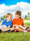 Boys Reading Books. Happy Kids, Young Boys Reading Books Outside Together after School Royalty Free Stock Photography