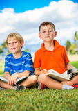 Boys Reading Books. Happy Kids, Young Boys Reading Books Outside Together after School Stock Photo