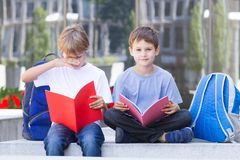 Boys reading books outdoors. Boys learning. Children reading books sitting on the bench outdoors Royalty Free Stock Photos