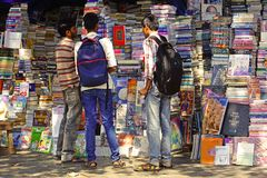 Boys reading the titles of books in the street. Royalty Free Stock Photos