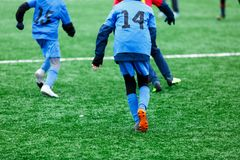 Boys in red and blue sportswear plays soccer on green grass field. Youth football game. Children sport competition. Kids plays outdoor, winter activities stock photo