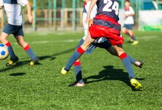 Boys in red blue sportswear running on soccer field. Young footballers dribble and kick football ball in game. Training,. Active lifestyle, sport, children royalty free stock images