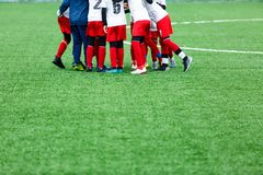 Boys in red and white sportswear plays soccer on green grass field. Youth football game. Children sport competition,. Kids plays outdoor, activities, training royalty free stock photography