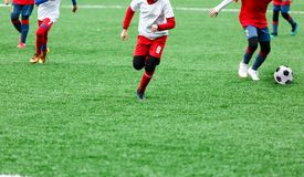 Boys in red and white sportswear plays soccer on green grass field. Youth football game. Children sport competition,. Kids plays outdoor, activities, training royalty free stock photo