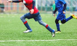 Boys in red white sportswear running on soccer field. Young footballers dribble and kick football ball in game. Training. Active lifestyle, sport, children stock photos