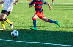 Boys in red white sportswear running on soccer field. Young footballers dribble and kick football ball in game. Training. Active lifestyle, sport, children royalty free stock photo