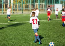 Boys in red white sportswear running on soccer field. Young footballers dribble and kick football ball in game. Training stock photos