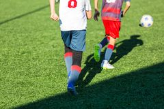 Boys in red white sportswear running on soccer field. Young footballers dribble and kick football ball in game. Training. Active lifestyle, sport, children royalty free stock photos
