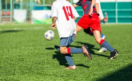 Boys in red white sportswear running on soccer field. Young footballers dribble and kick football ball in game. Training,. Active lifestyle, sport, children royalty free stock photo