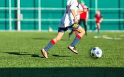 Boys in red white sportswear running on soccer field. Young footballers dribble and kick football ball in game. Training. Active lifestyle, sport, children stock photography