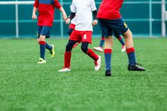 Boys in red white sportswear running on soccer field. Young footballers dribble and kick football ball in game. Training. Active lifestyle, sport, children royalty free stock image