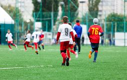 Boys in red white sportswear running on soccer field. Young footballers dribble and kick football ball in game. Training. Active lifestyle, sport, children stock photo