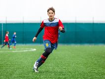 Boys in red white sportswear running on soccer field. Young footballers dribble and kick football ball in game. Training. Active lifestyle, sport, children royalty free stock images