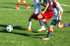 Boys in red white sportswear running on soccer field. Young footballers dribble and kick football ball in game. Training,. Active lifestyle, sport, children stock photos