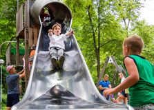 Boys ride on the slide of the playground stock photo