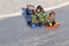 Boys are riding on an icy hill. Royalty Free Stock Photography
