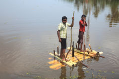 Boys rows a raft made out of banana stem in the backwaters Royalty Free Stock Images