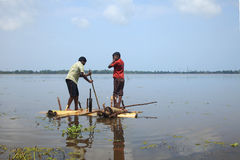 Boys rows a raft made out of banana stem in the backwaters Royalty Free Stock Photography