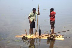 Boys rows a raft made out of banana stem in the backwaters Stock Photo