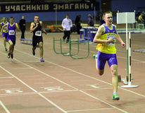 Boys run 400 meters race. Pozdnikov Aleksei  run on the finish of the 400 m. race on Ukrainian Junior Track and Field Championships on January 31, 2012 in Stock Photography
